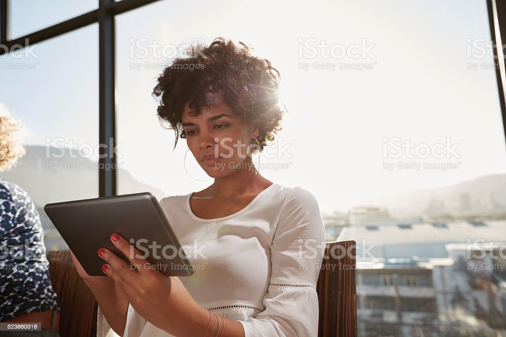 Young woman busy working on digital tablet stock photo
