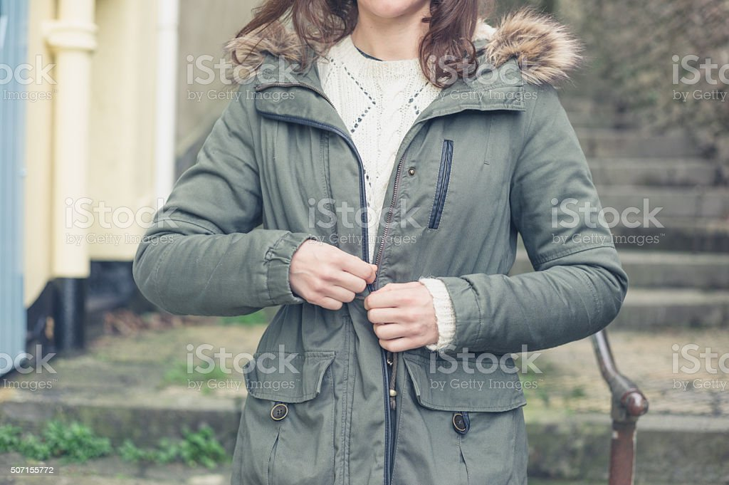 Young woman buttoning her coat outside stock photo