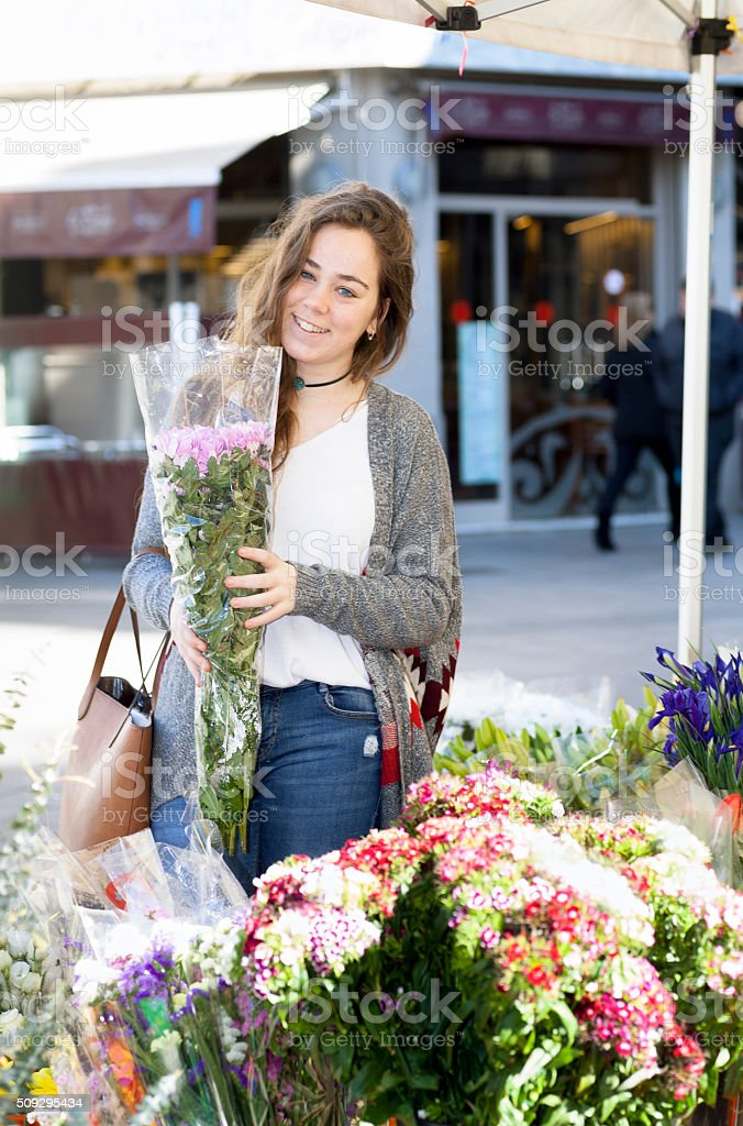 Young woman buying a bouquet in a flower market stock photo
