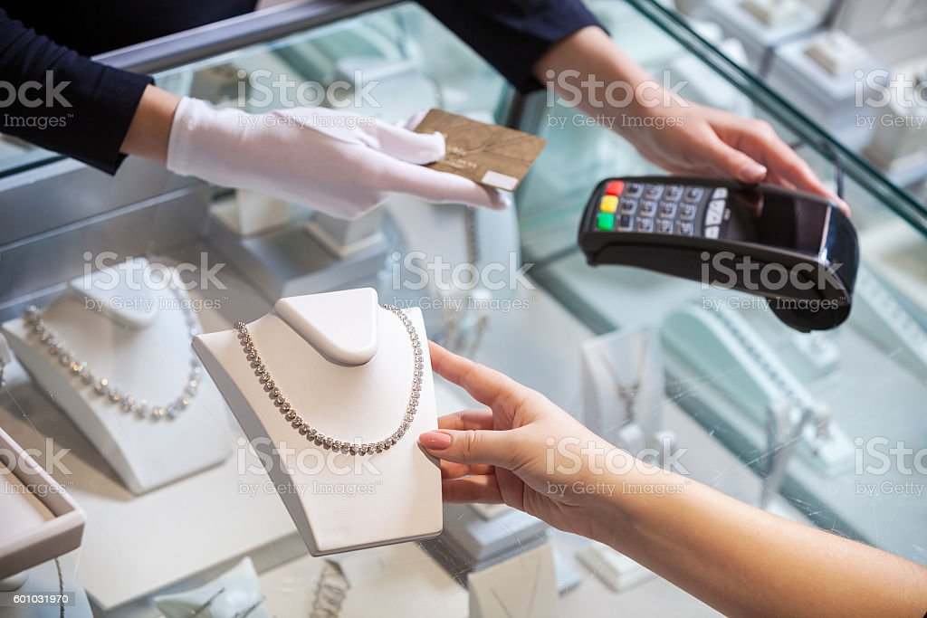 Young woman buying a golden diamond necklace stock photo
