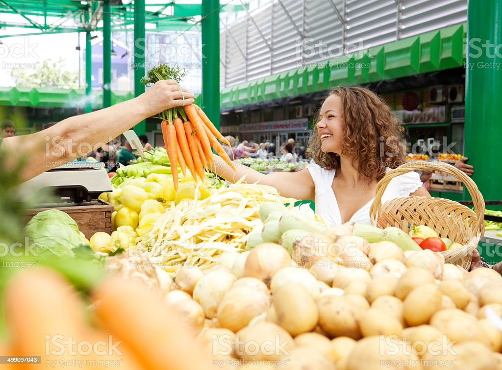 Young Woman Buying Carrots at Grocery Market stock photo