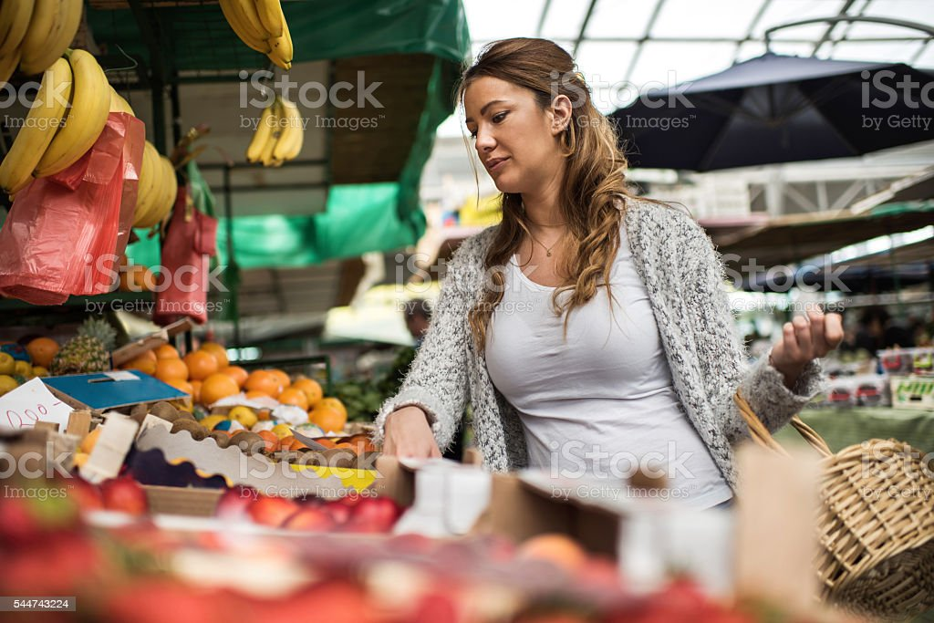 Young woman buying fresh fruits at farmer's market. stock photo