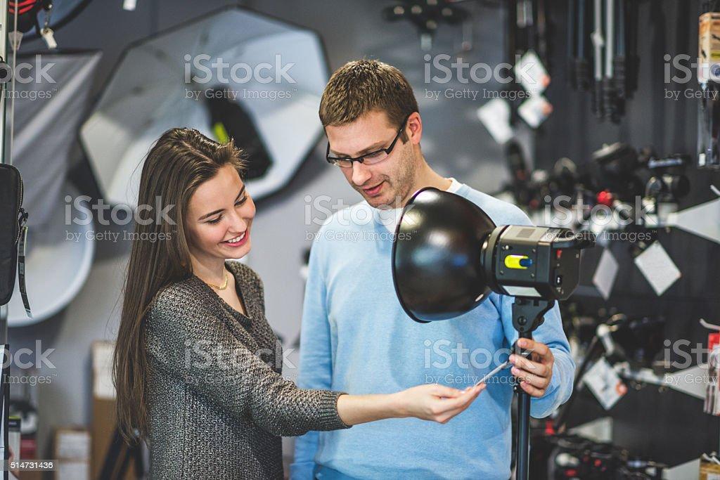 Young woman buying lighting equipment stock photo