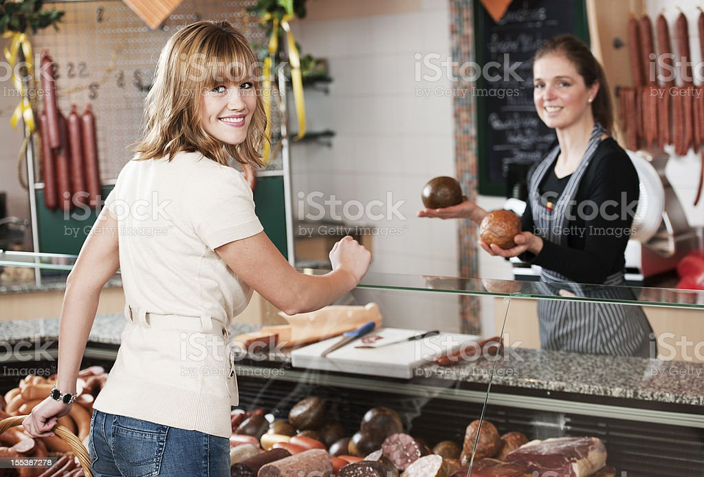 Young woman buying sausage royalty-free stock photo