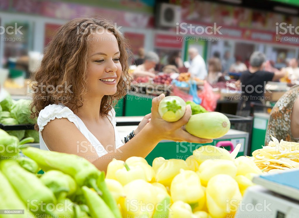 Young Woman Buying Squashes at Grocery Market stock photo