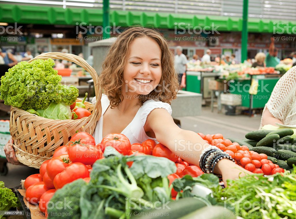 Young Woman Buying Vegetables at Grocery Market stock photo