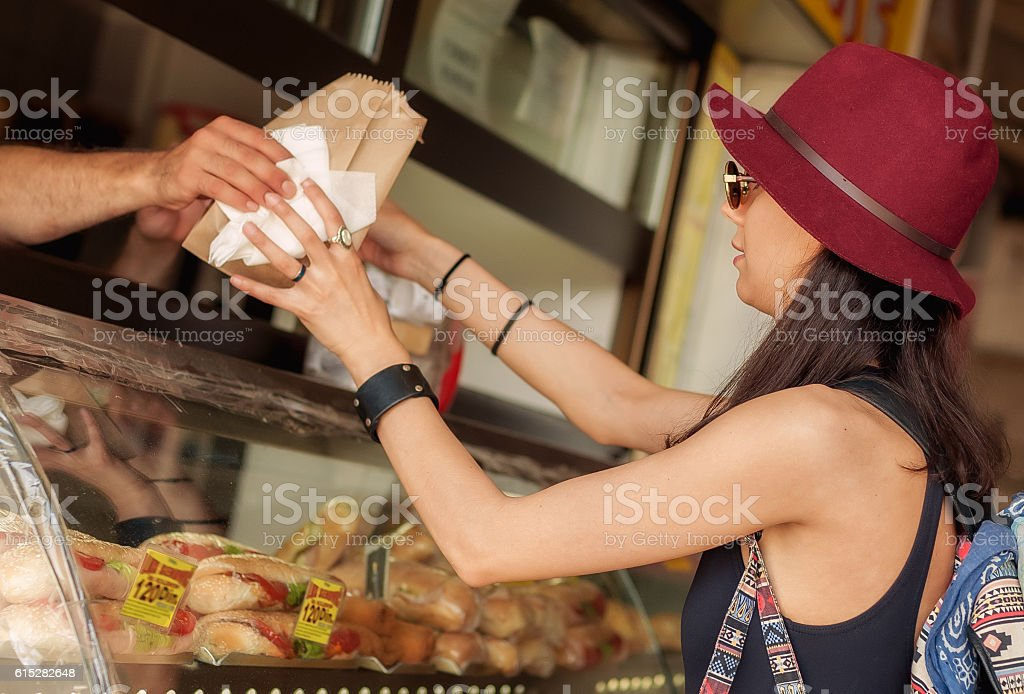 Young woman buys fresh pastries at bakery market stock photo