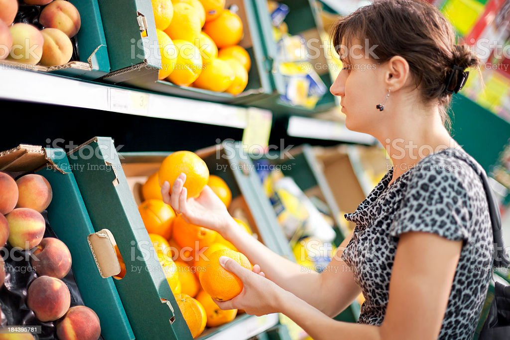 Young woman buys oranges in a supermarket royalty-free stock photo