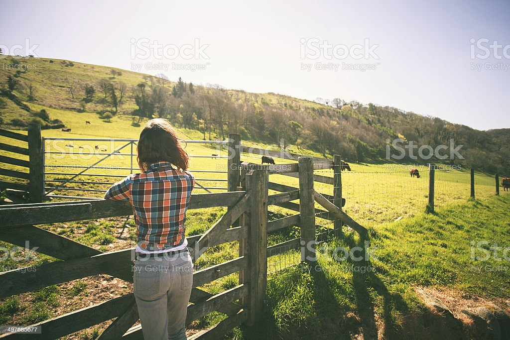 Young woman by a fence on a ranch stock photo