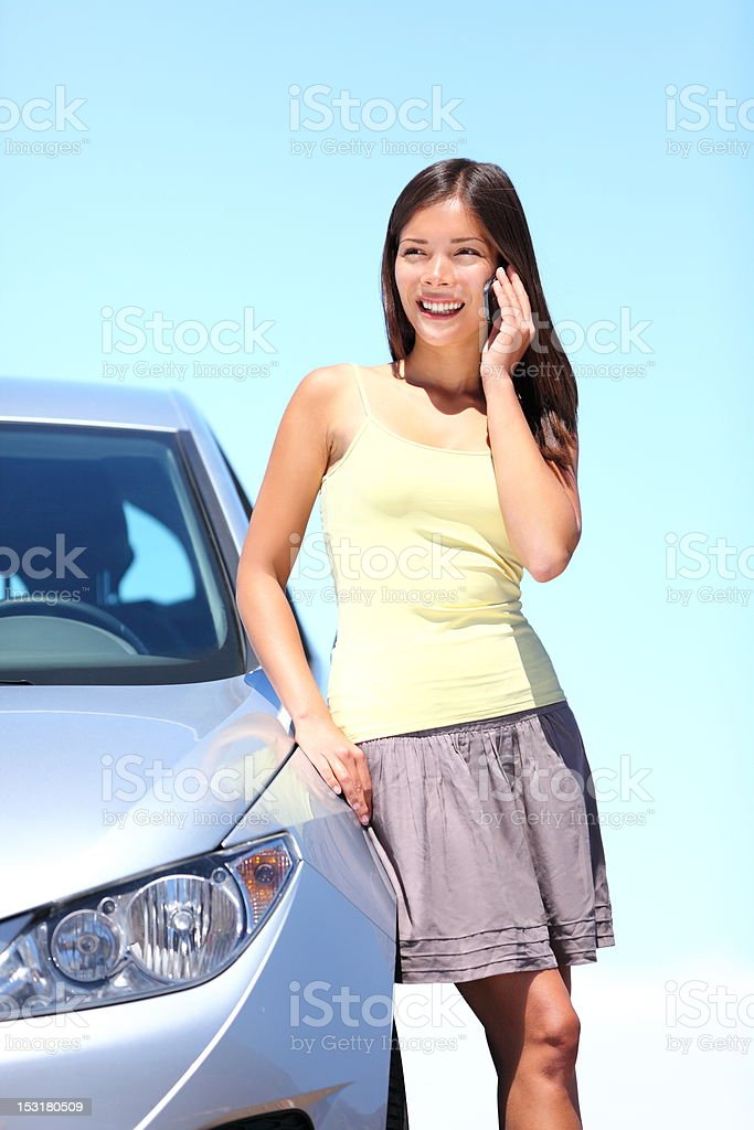 Young woman by car on mobile phone royalty-free stock photo