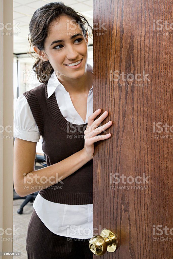 Young woman by door stock photo
