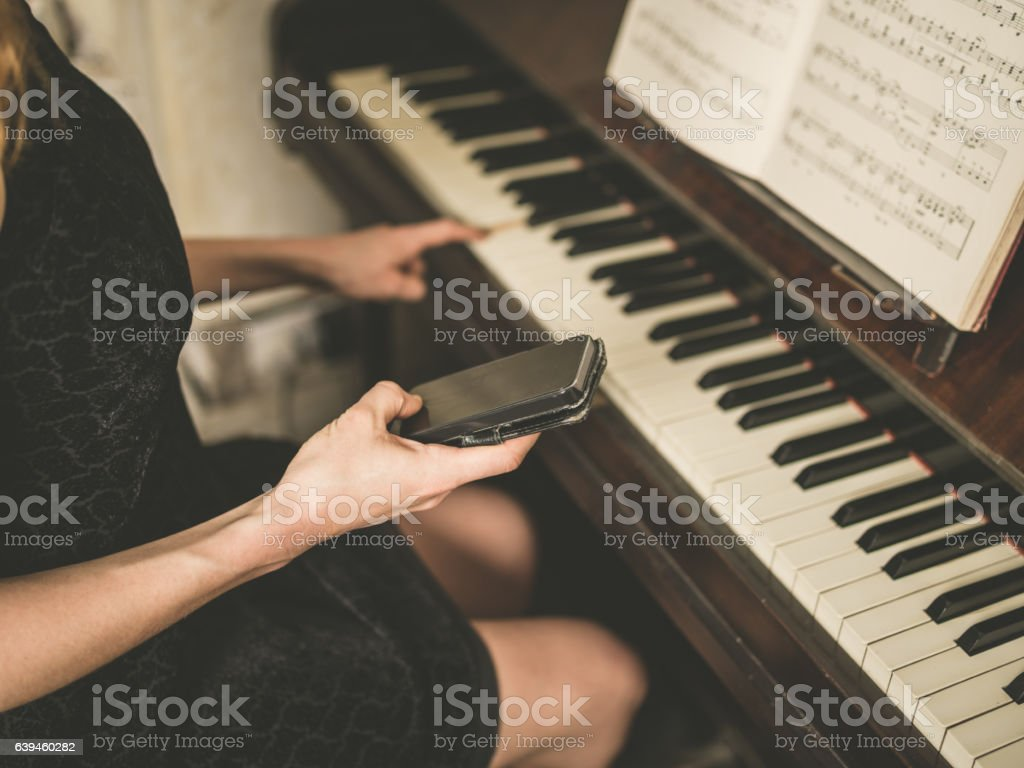 Young woman by piano with smart phone stock photo