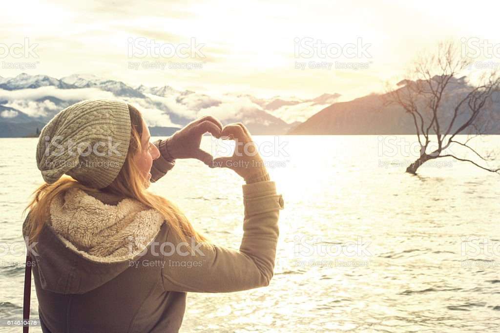 Young woman by the lake makes heart shape finger frame stock photo
