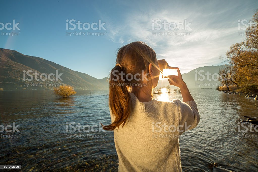 Young woman by the lake making a finger frame stock photo