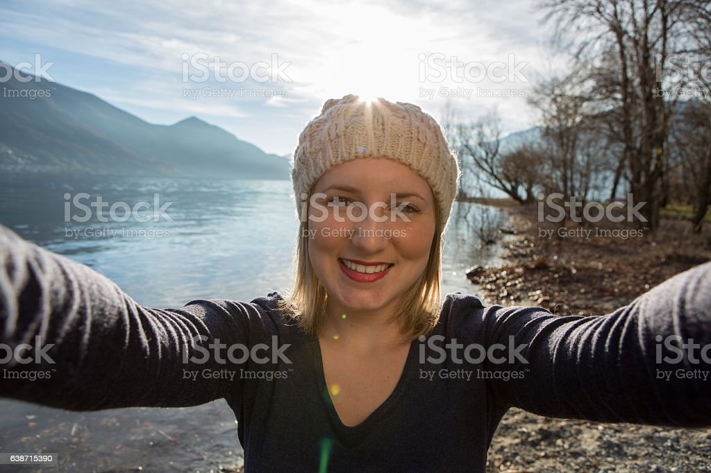 Young woman by the lake takes a selfie portrait stock photo