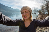 Young woman by the lake takes a selfie portrait