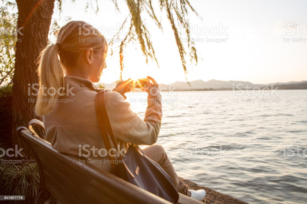 Young woman by the lake using mobile phone stock photo