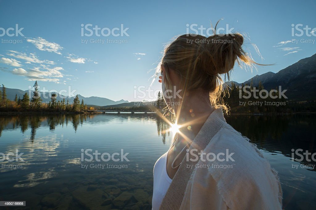 Young woman by the lake watching the sunset. stock photo