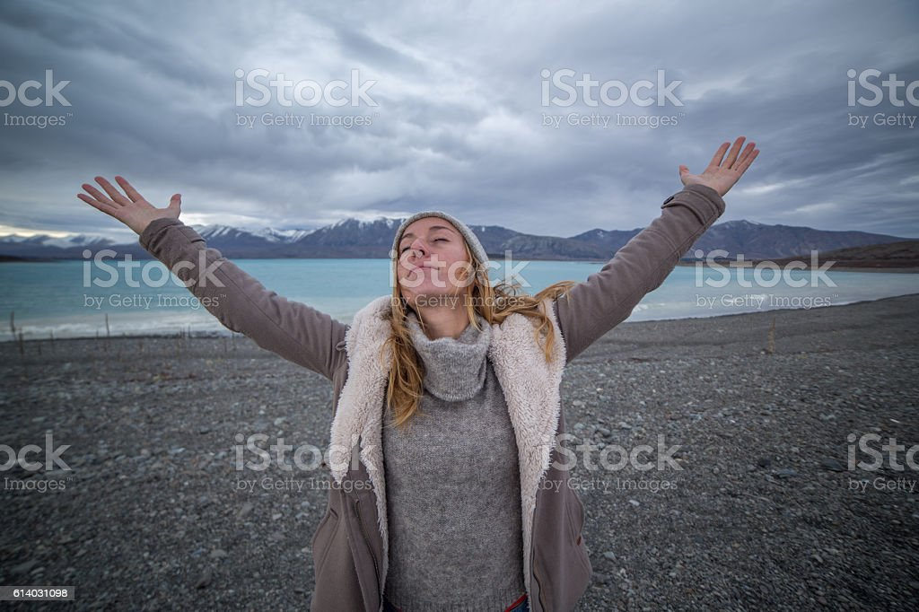 Young woman by the lakeshore arms outstretched stock photo
