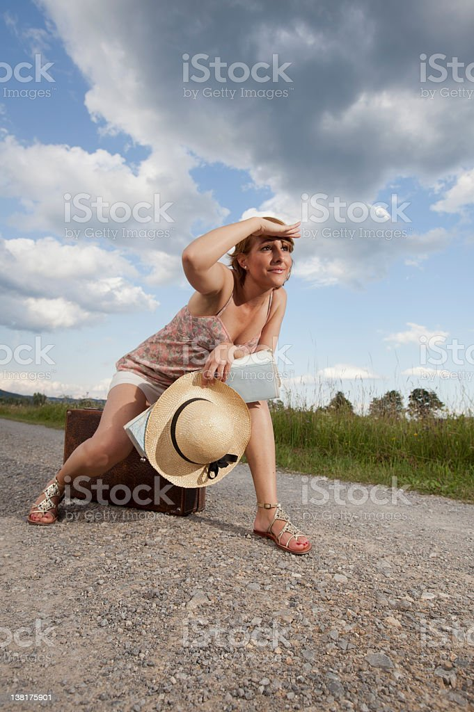Young woman by the road with suitcase stock photo