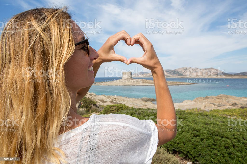 Young woman by the sea makes heart shape finger frame stock photo