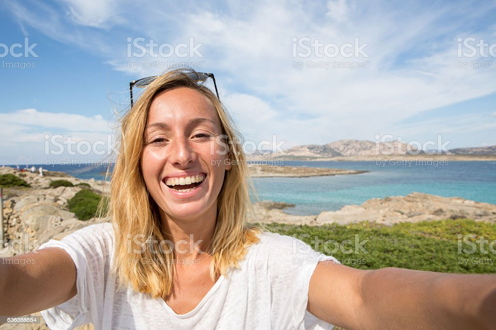 Young woman by the sea takes a selfie portrait stock photo