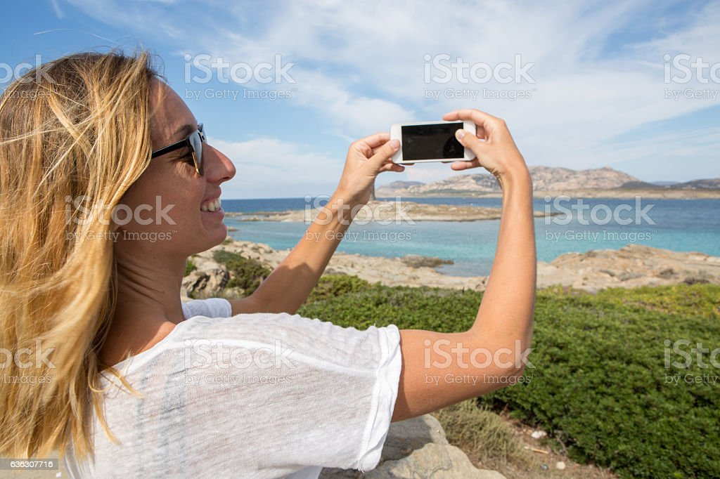 Young woman by the sea takes smart phone picture, Italy stock photo