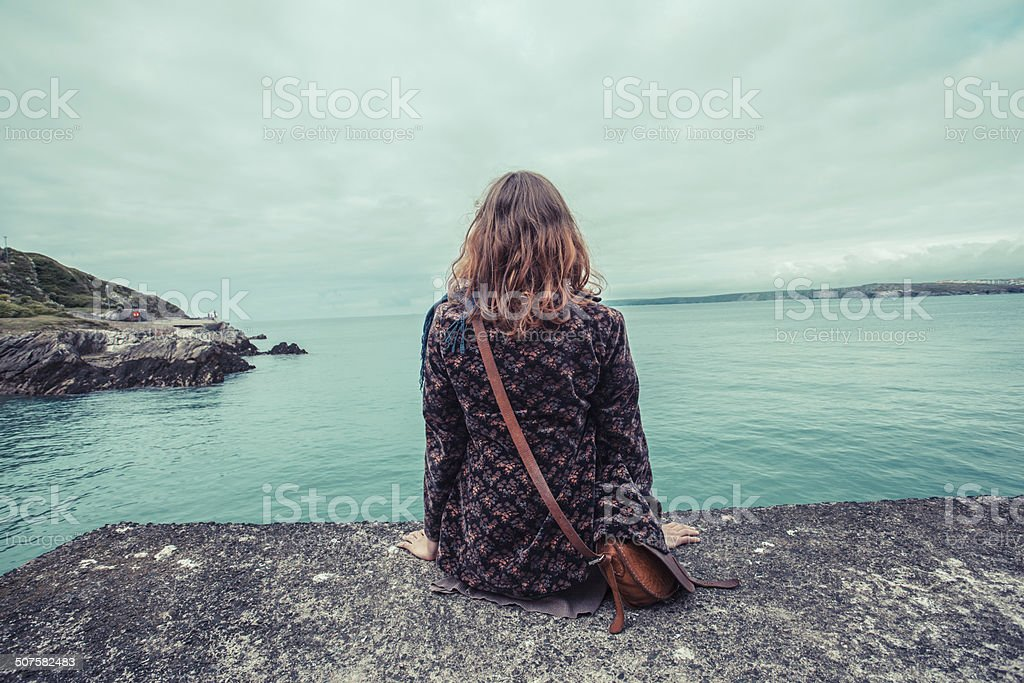 Young woman by the water's edge stock photo