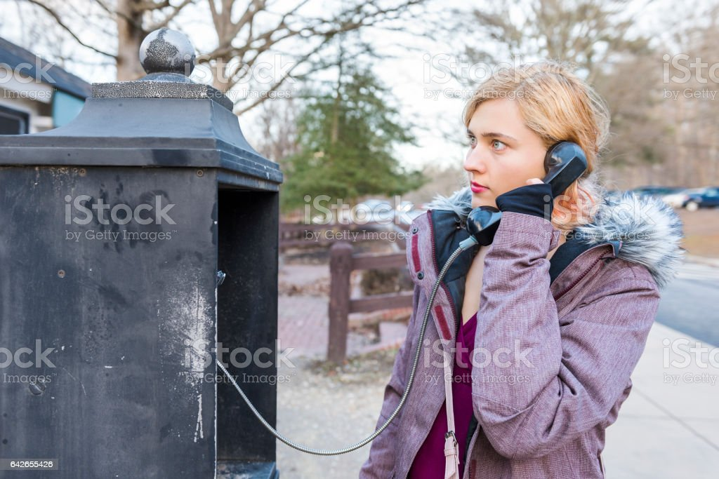 Young woman calling in phonebooth in winter stock photo