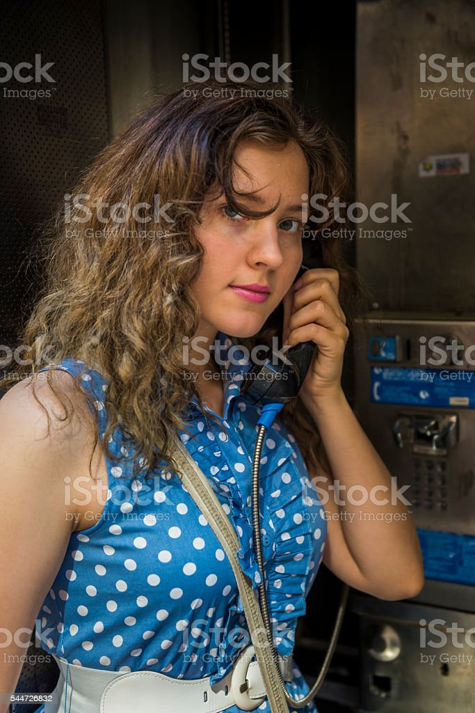 Young woman calling in phonebooth stock photo