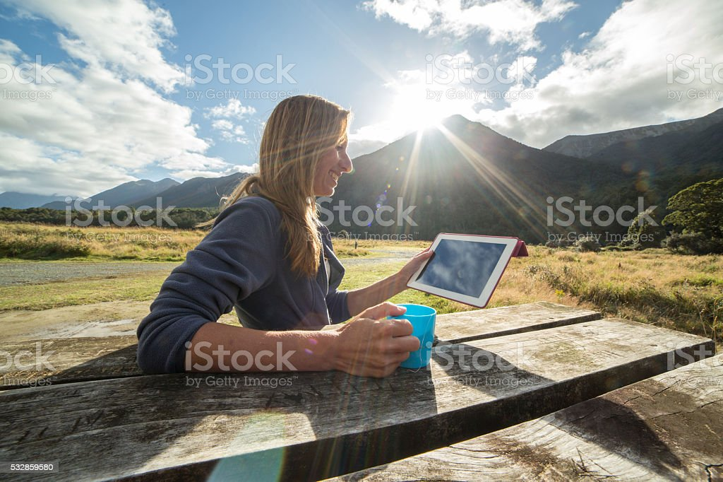 Young woman camping, uses a digital tablet stock photo