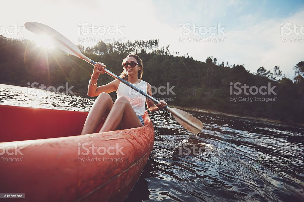 Young woman canoeing in a lake stock photo