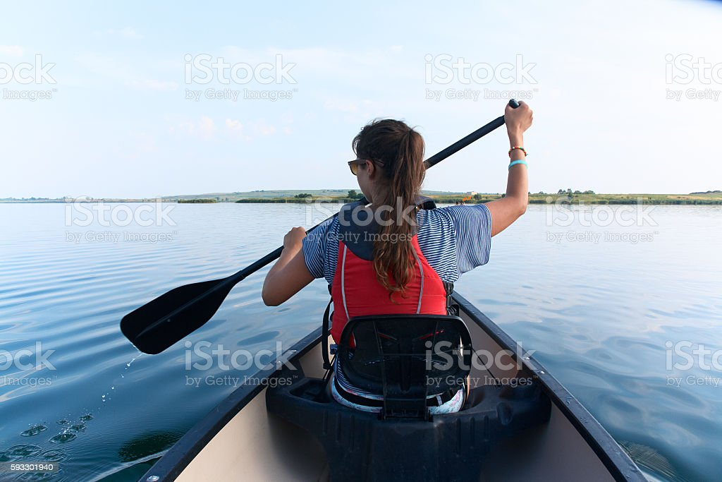 Young woman canoeing in the lake on a summer day. stock photo