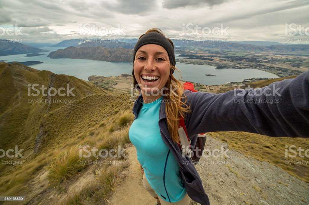 Young woman captures her success of reaching mountain top stock photo