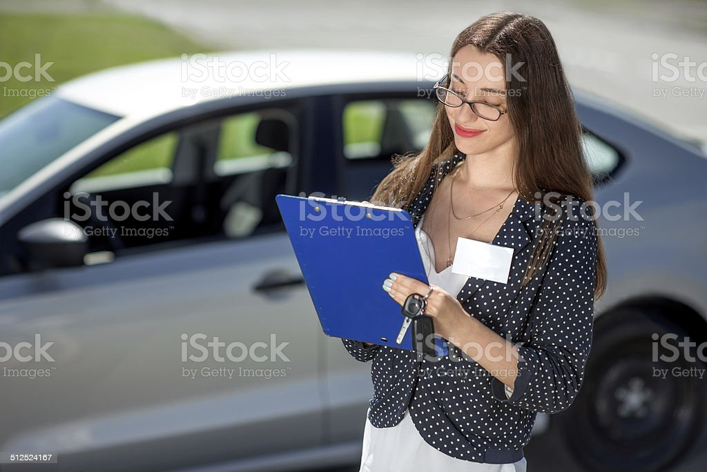 Young woman car rental inspector filling contract stock photo