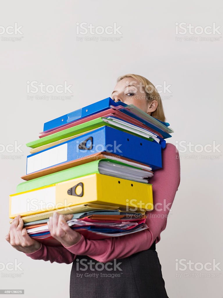 Young woman carry a heavy load of work materials stock photo