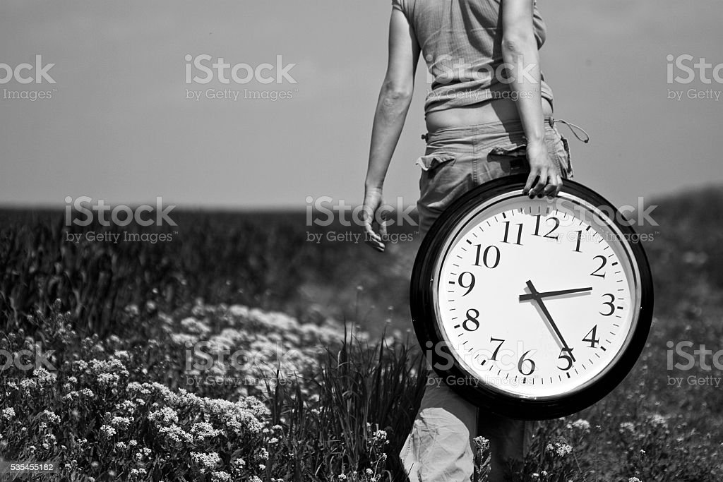 Young woman carrying a big clock on a field stock photo
