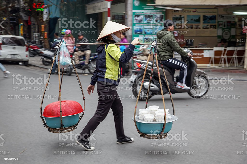 Young woman carrying a street kitchen in Hanoi stock photo