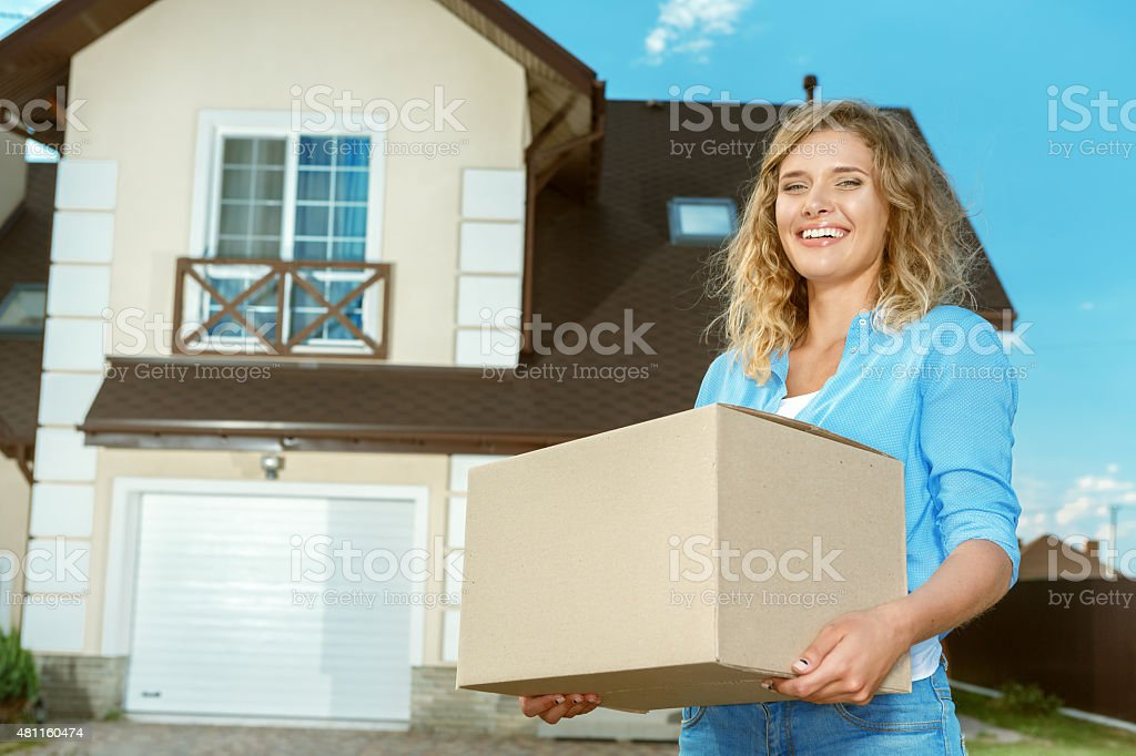 Young woman carrying boxes in to new house stock photo
