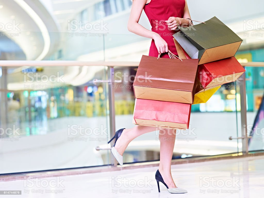 young woman carrying colorful paper bags walking in shopping mall stock photo