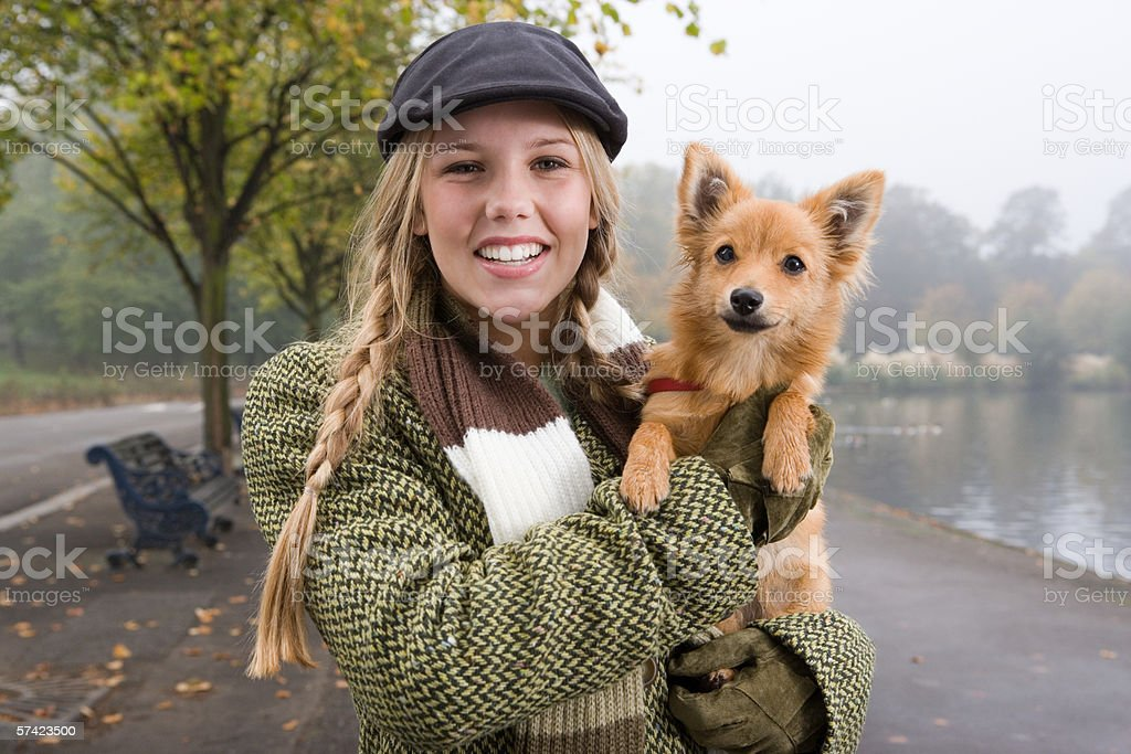 Young woman carrying dog in the park stock photo