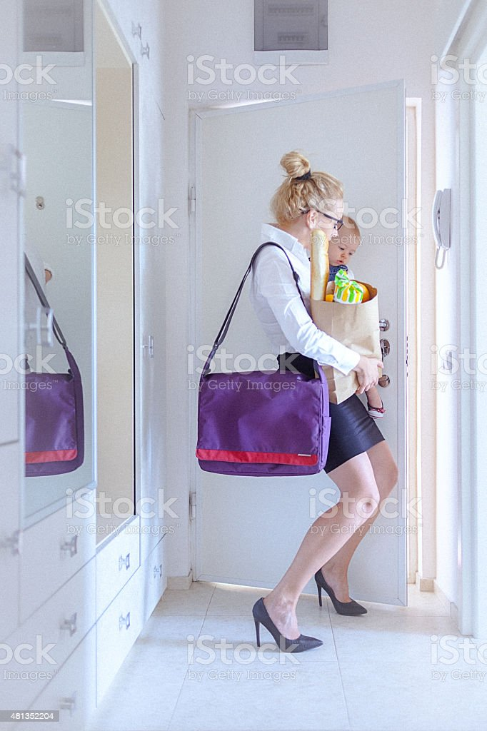 Young woman carrying grocery and her baby closes the door stock photo