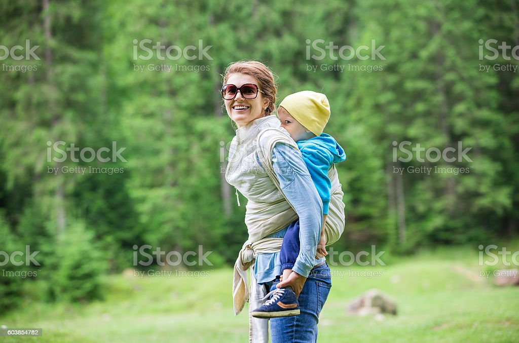 Young woman carrying her toddler son in woven wrap stock photo