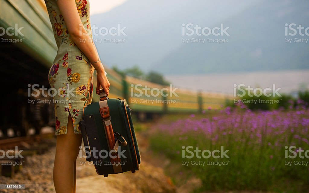 Young woman carrying luggage in old retro vintage train stock photo