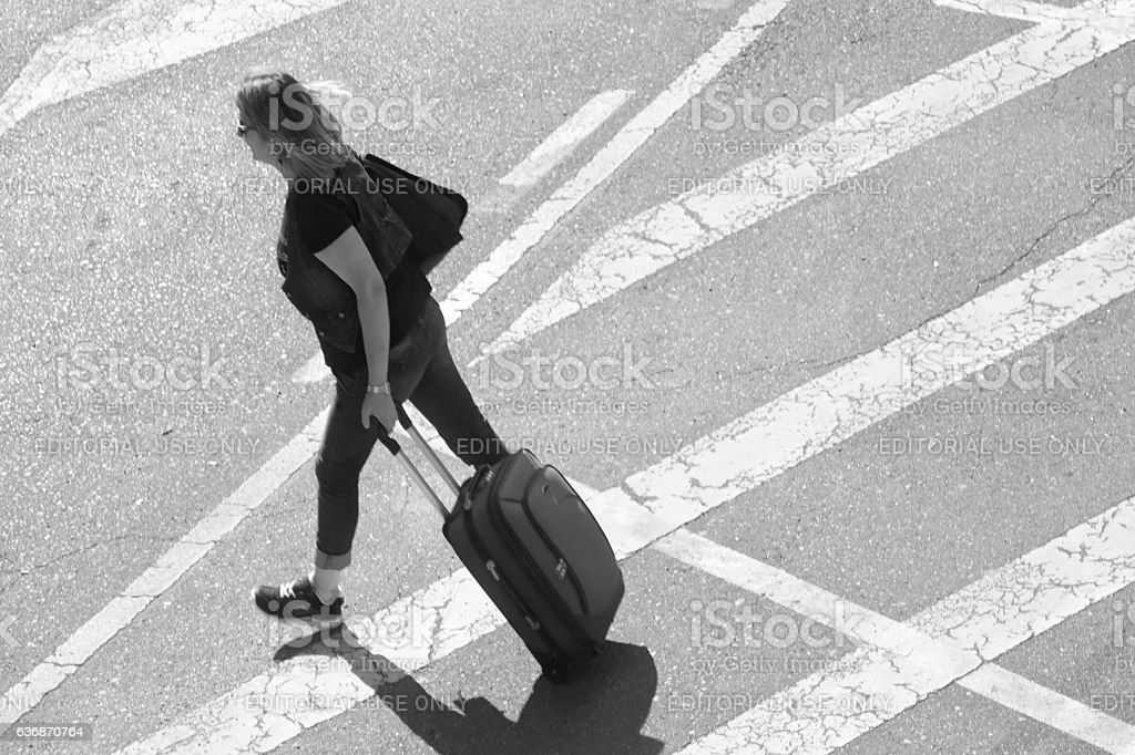 Young woman carrying luggage in the street stock photo