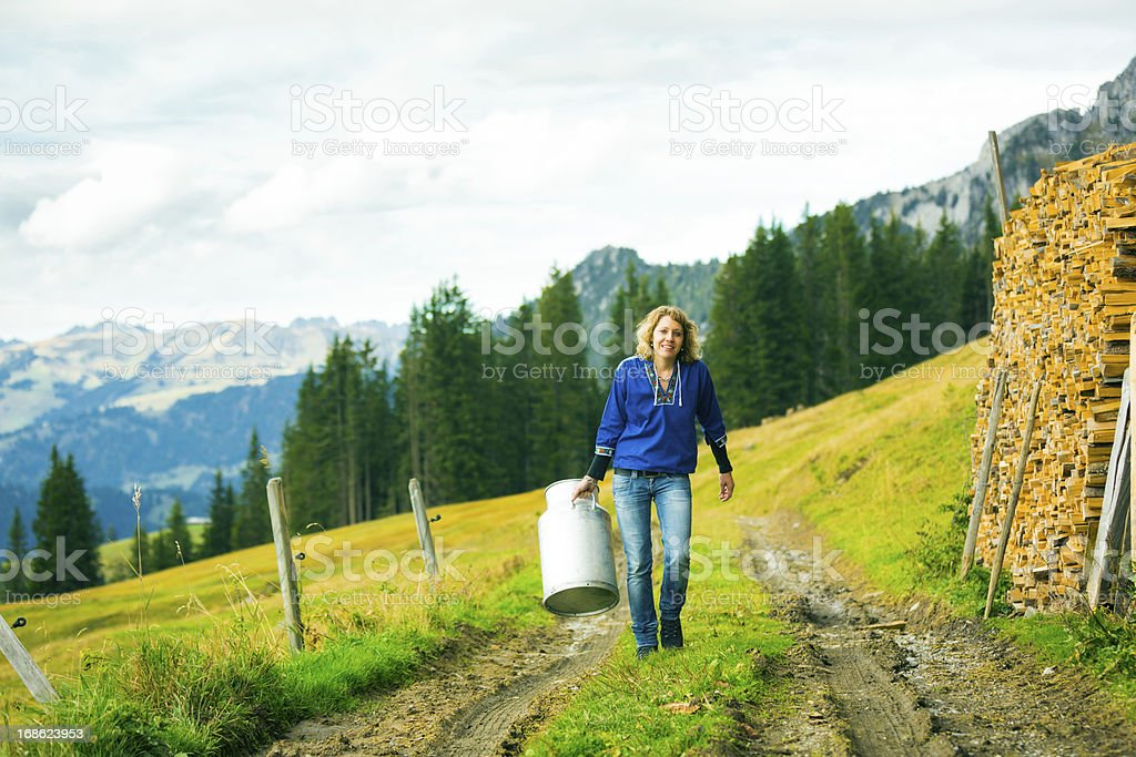 young woman carrying milk canister stock photo