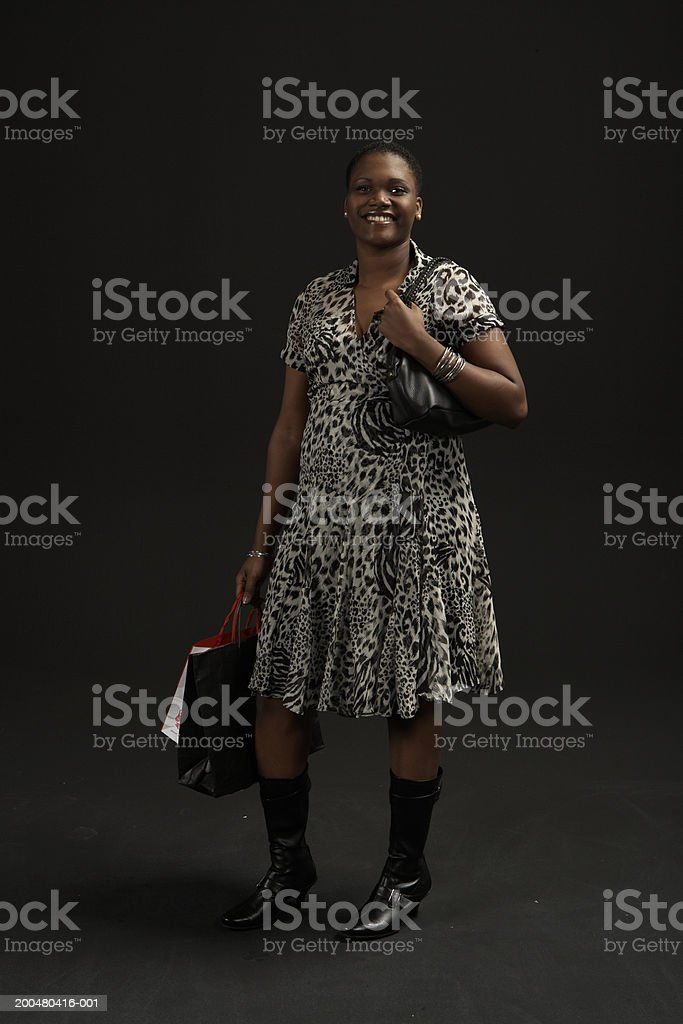 Young woman carrying purse and shopping bags, smiling, portrait stock photo