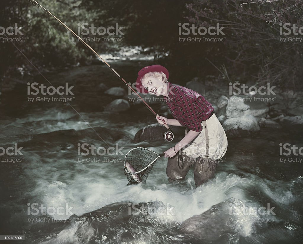 Young woman catching fish in stream, smiling, portrait stock photo