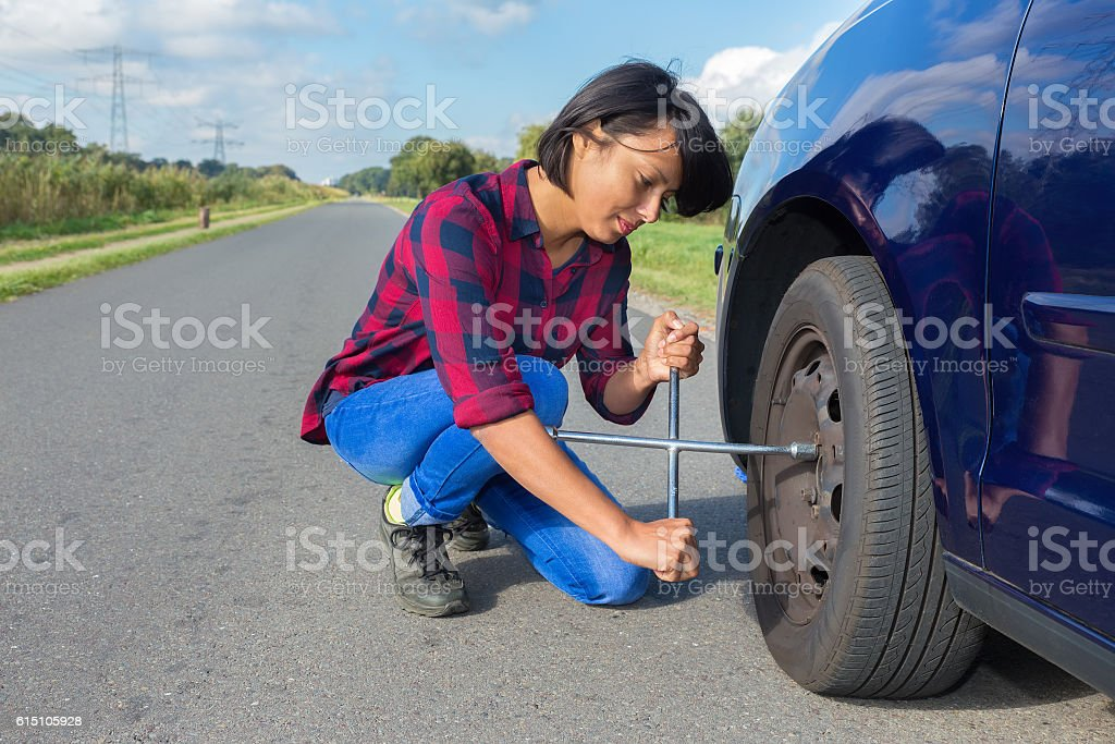 Young woman changing car wheel on country road stock photo