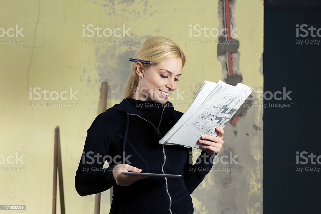 Young woman checking blueprints for home renovation royalty-free stock photo